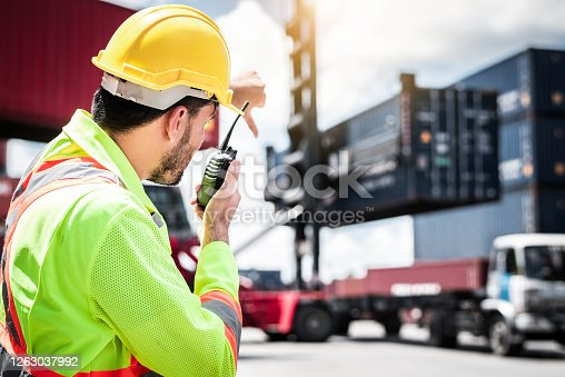 Confident Caucasian man engineer wearing yellow safety helmet using walkies talkie call to driver and check for control loading containers box from Cargo freight ship for import and export, transport