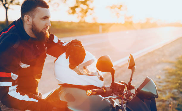 Confident caucasian man with a big beard sitting on his motorbike putting his hand on the white helmet while sun is warming him stock photo