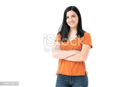 Smiling attractive young woman standing with arms crossed against white background