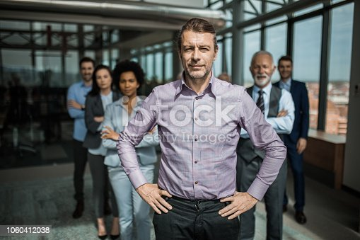 Confident mid adult businessman standing in front of his team with hands on hips and looking at camera.
