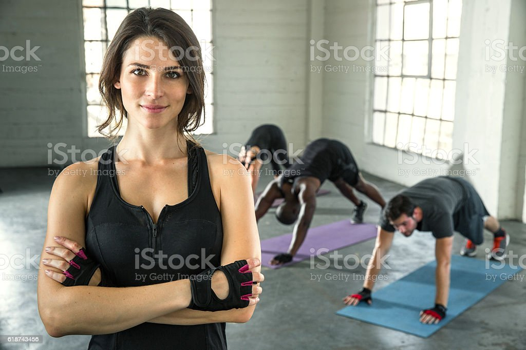 Confident cheerful beautiful physical fitness exercise trainer smiling successful stock photo