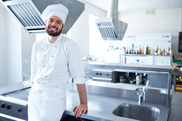 Confident chef at restaurant kitchen Positive handsome male chef with beard wearing white uniform leaning on kitchen counter and looking at camera chef's whites stock pictures, royalty-free photos & images