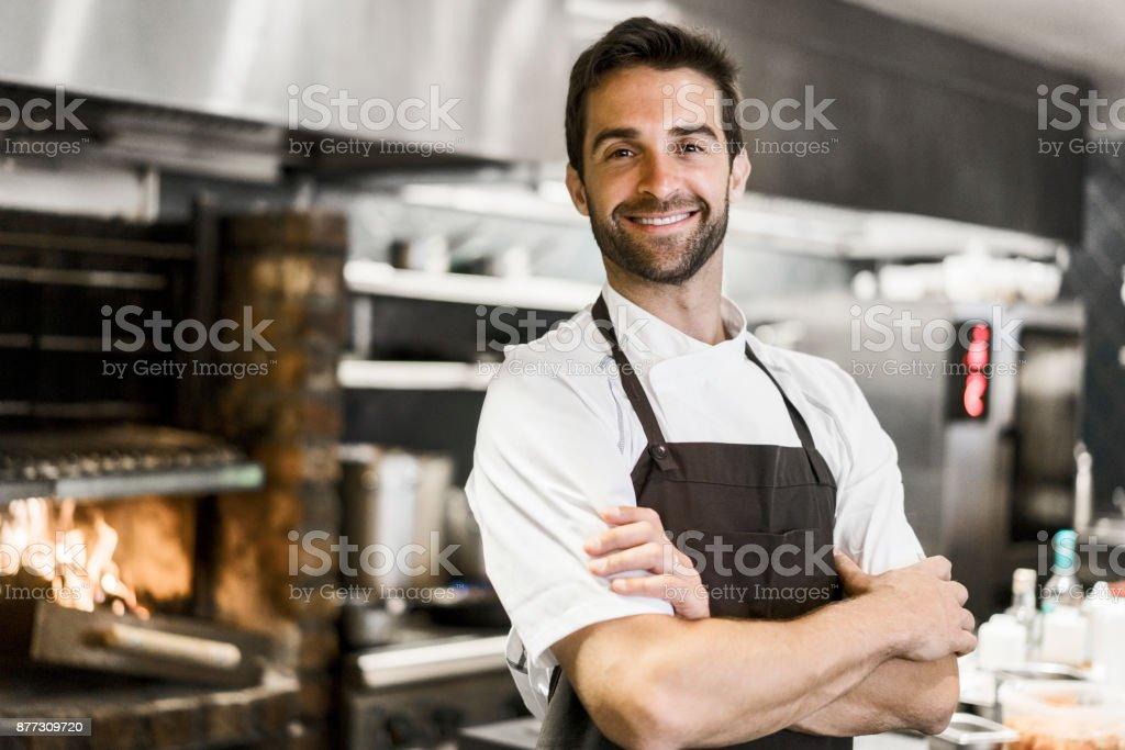 Chef seguro de brazos de pie cruzan en cocina - foto de stock