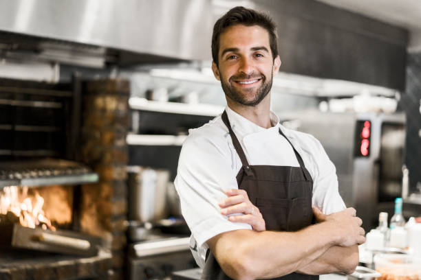 Confident chef standing arms crossed in kitchen stock photo