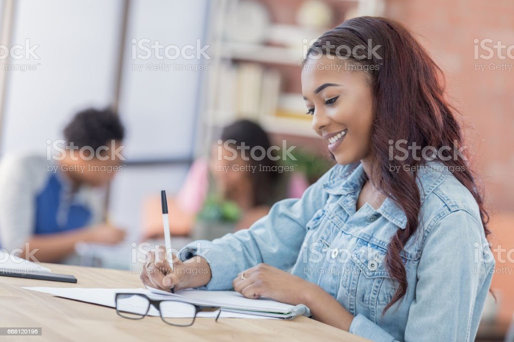 Confident college girl wrks on assignment in library stock photo