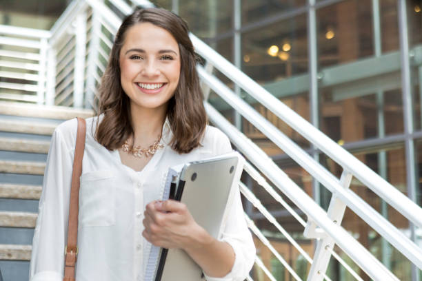 Confident college student on her way to class Attractive Hispanic female college student holds books and a laptop while walking to class on the university campus. A staircase is in the background. adult student stock pictures, royalty-free photos & images