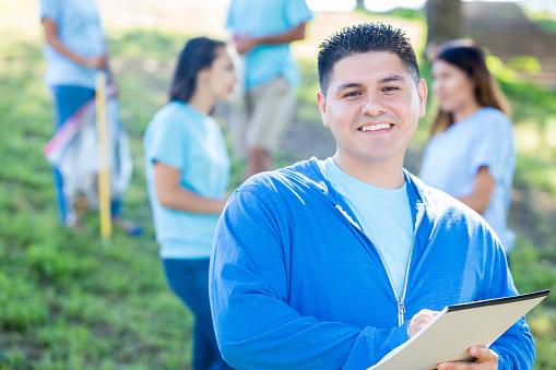 Confident community cleanup event organizer organizes volunteers