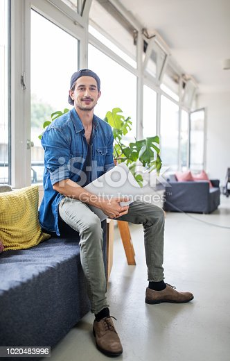 Portrait of young businessman smiling. Confident computer programmer sitting in office lounge.