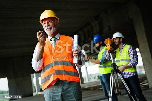 Confident senior construction engineer, architect, businessman working on building site