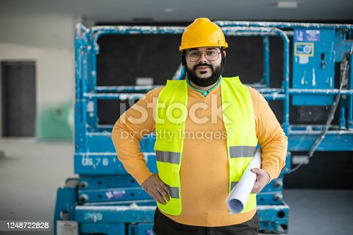 Confident male, overweight construction worker wearing hardhat and reflective clothing, standing at construction site, holding blueprint and looking at camera