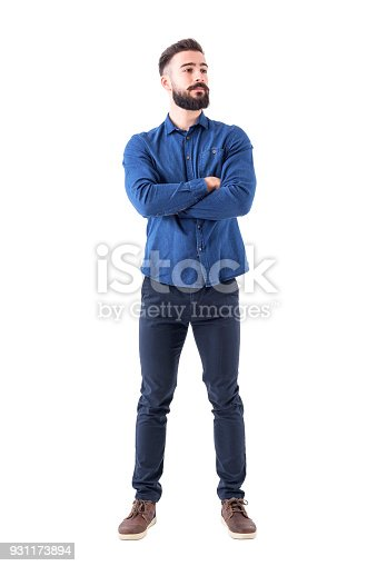 931173966istockphoto Confident cool young bearded man standing and looking away with crossed hands 931173894