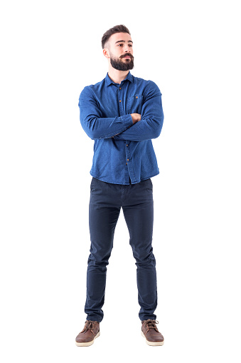 931173966 istock photo Confident cool young bearded man standing and looking away with crossed hands 931173894