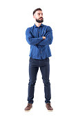 istock Confident cool young bearded man standing and looking away with crossed hands 931173894