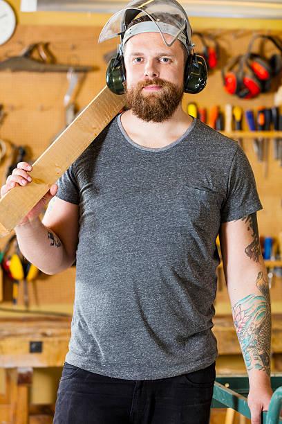 zuversichtlich handwerker mit sicherheit maske und ohrenschützer in workshops - baroque tattoo stock-fotos und bilder
