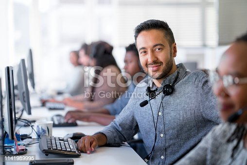 Portrait of confident customer support operator at desk. Handsome male is working with colleagues in call center. He is wearing hands-free device at workplace.
