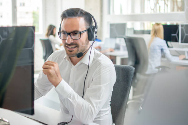 Confident customer support phone operator with headset working in call center stock photo