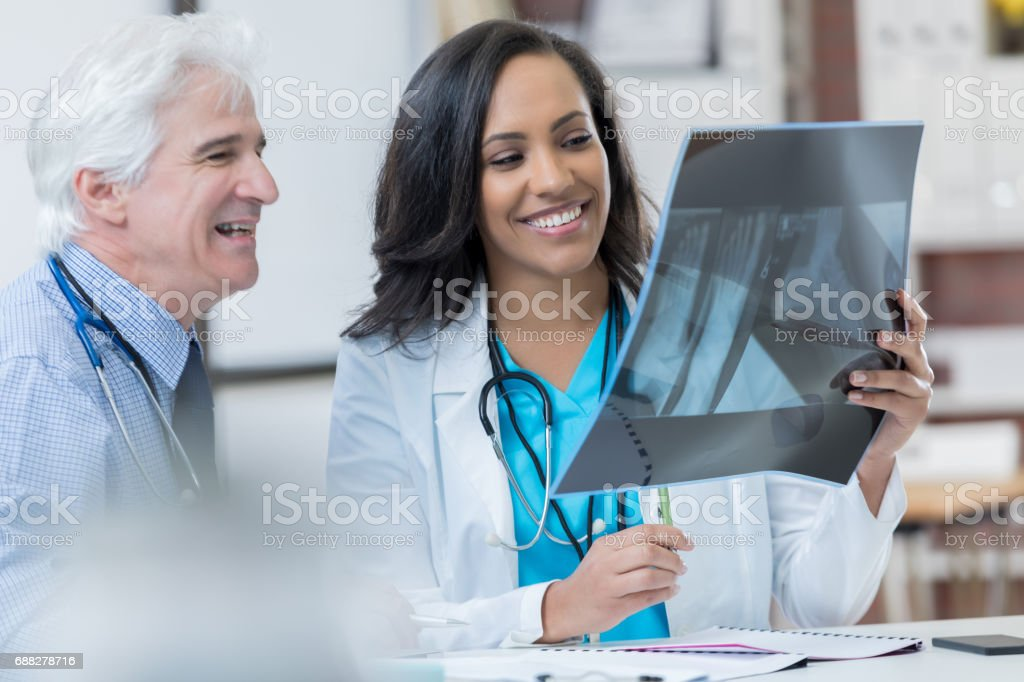 Confident diverse physicians review patient's x-ray stock photo