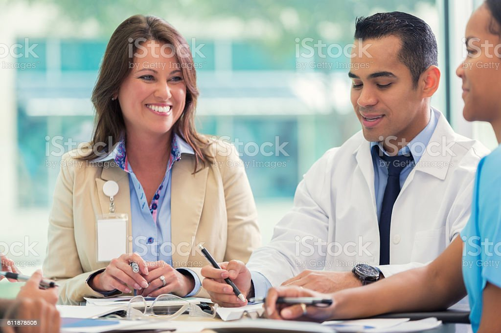Confident doctor and hospital executive discuss strategy stock photo