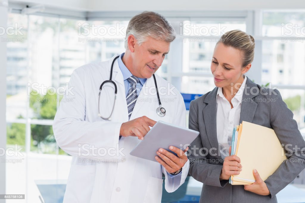 Confident doctor and pretty businesswoman discussing stock photo