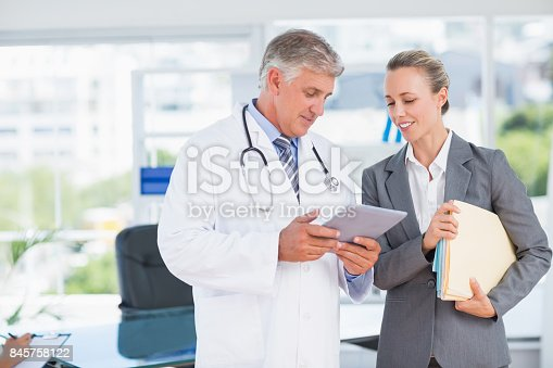 istock Confident doctor and pretty businesswoman discussing 845758122