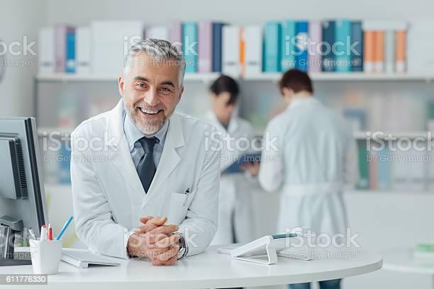 Confident Doctor At The Reception Desk Stockfoto und mehr Bilder von Arbeiten