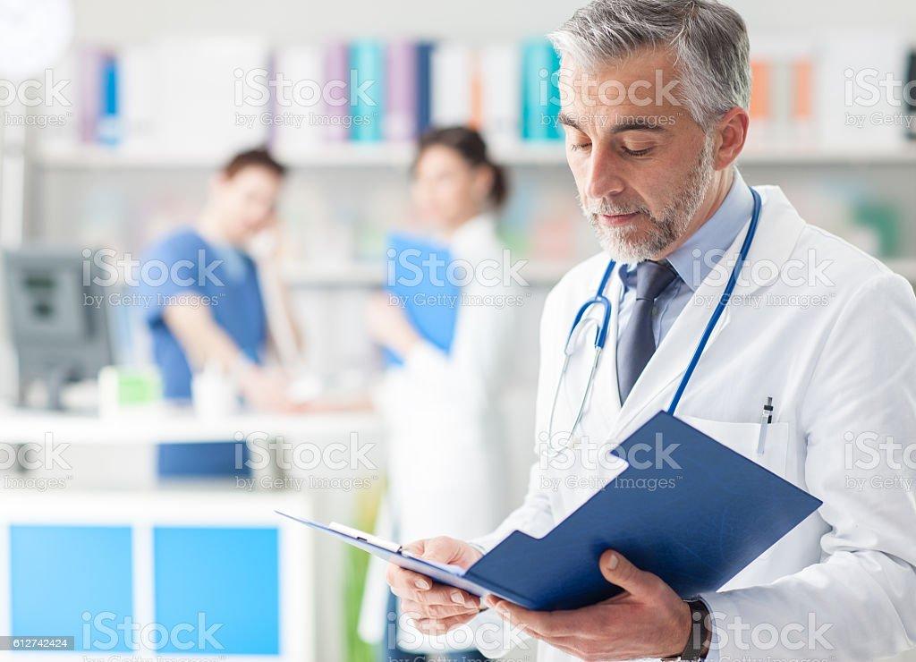 Confident doctor checking medical records - foto de acervo