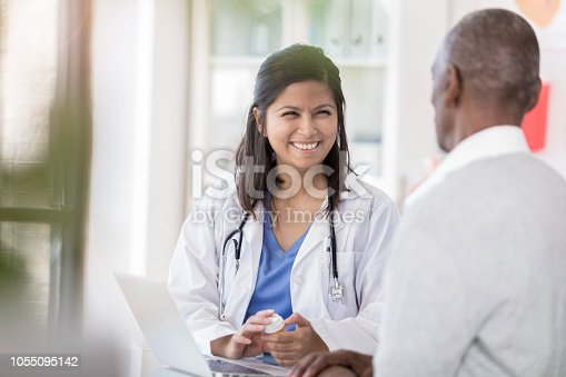 Smiling female doctor talks with senior male patient about his medication. She is holding a prescription medication bottle.