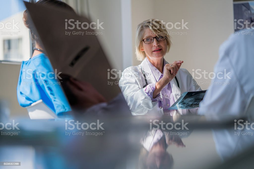 Confident doctor discussing with colleagues stock photo
