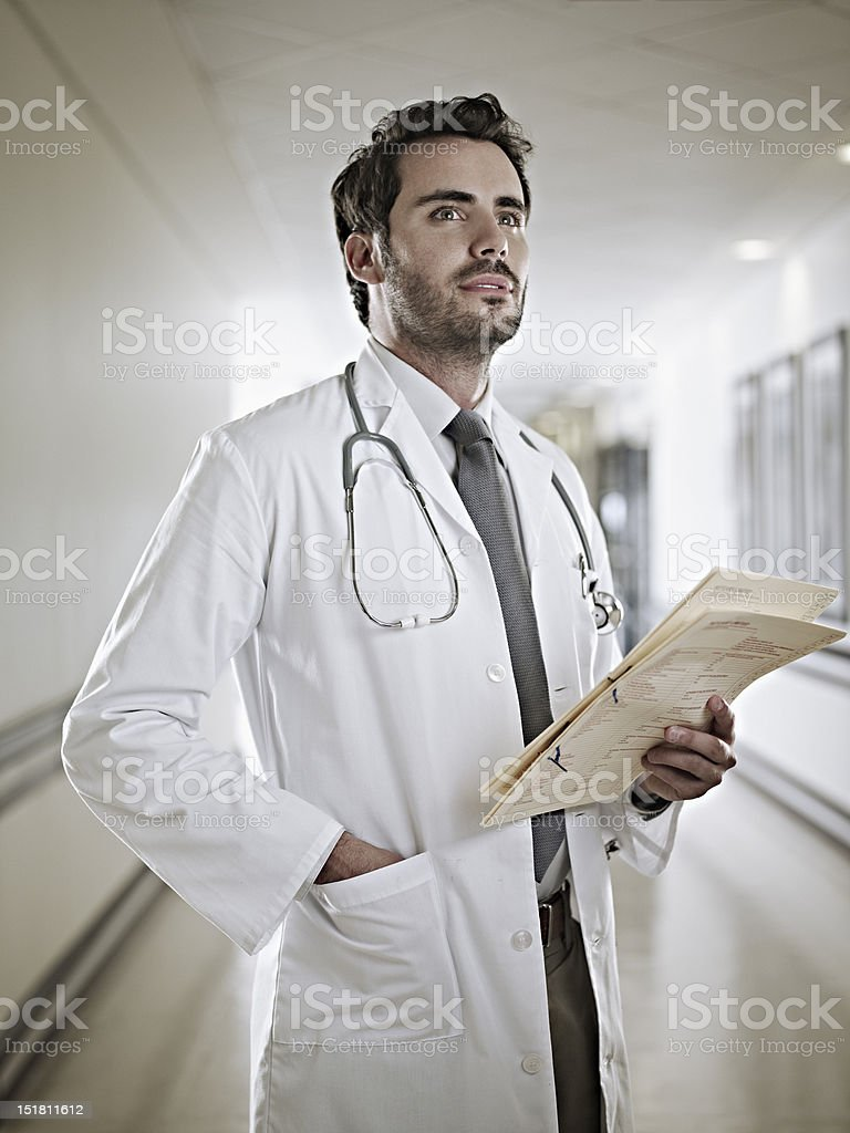 Confident doctor holding medical record in hospital corridor stock photo