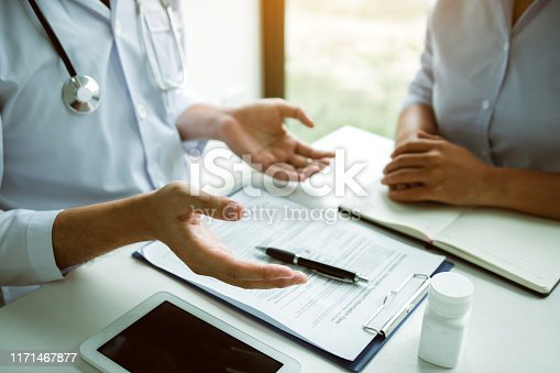 1026367516 istock photo Confident doctor man holding a pill bottle and writing while talking with senior patient and reviewing his medication at office room. 1171467877