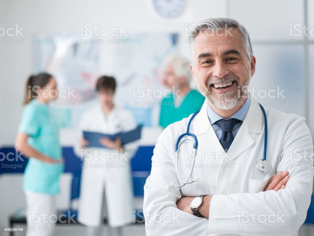 Confident doctor posing at the hospital stock photo