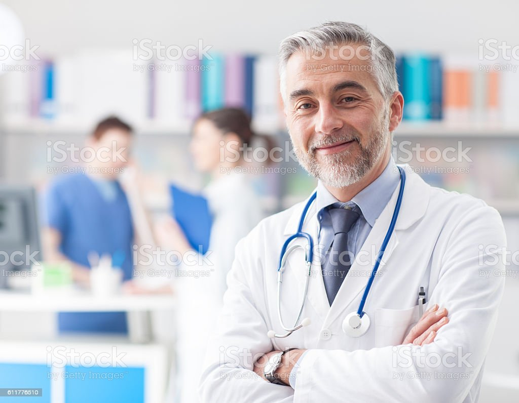 Confident doctor posing in the office stock photo