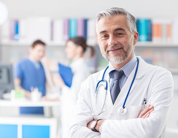confident doctor posing in the office - physician stock photos and pictures