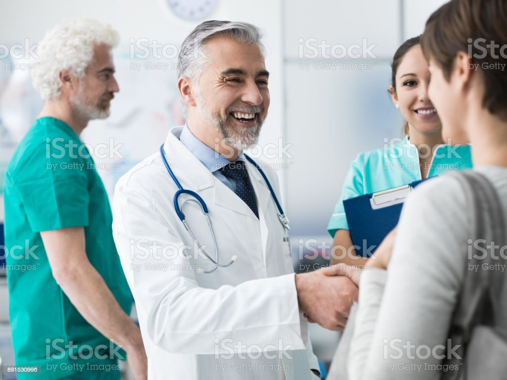 Confident doctor shaking patient's hand stock photo