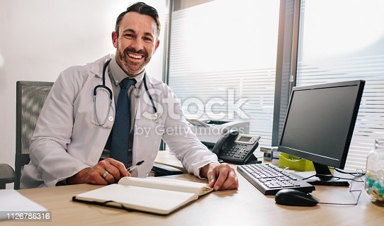 Confident doctor sitting at his desk with computer and diary. Doctor sitting at his desk with book and desktop computer in his office