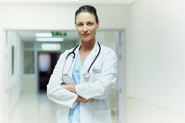 Confident doctor standing arms crossed Portrait of confident female doctor standing arms crossed in hospital female doctor stock pictures, royalty-free photos & images