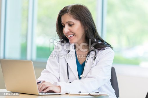 Confident mature female doctor uses a laptop in her office. She is adding information to a patients electronic file.
