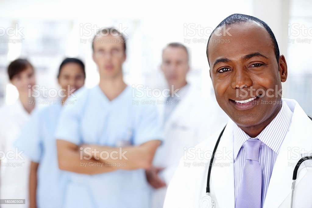 Confident doctor with medical team in background royalty-free stock photo