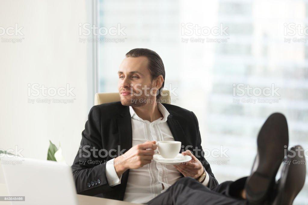 Confiant rêve homme d'affaires relaxant avec une tasse de café au travail. - Photo