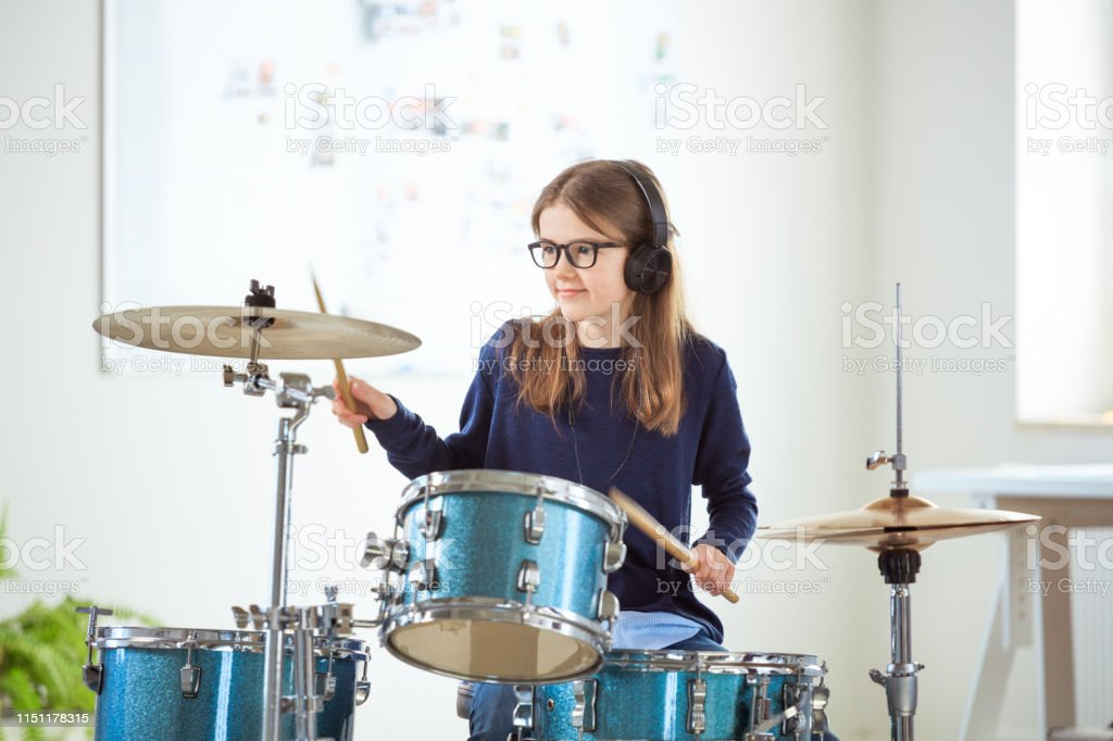 Confident drummer practicing in training class Confident student listening music through headphones while playing drums. Female drummer is practicing in classroom. She is training at conservatory. 10-11 Years Stock Photo