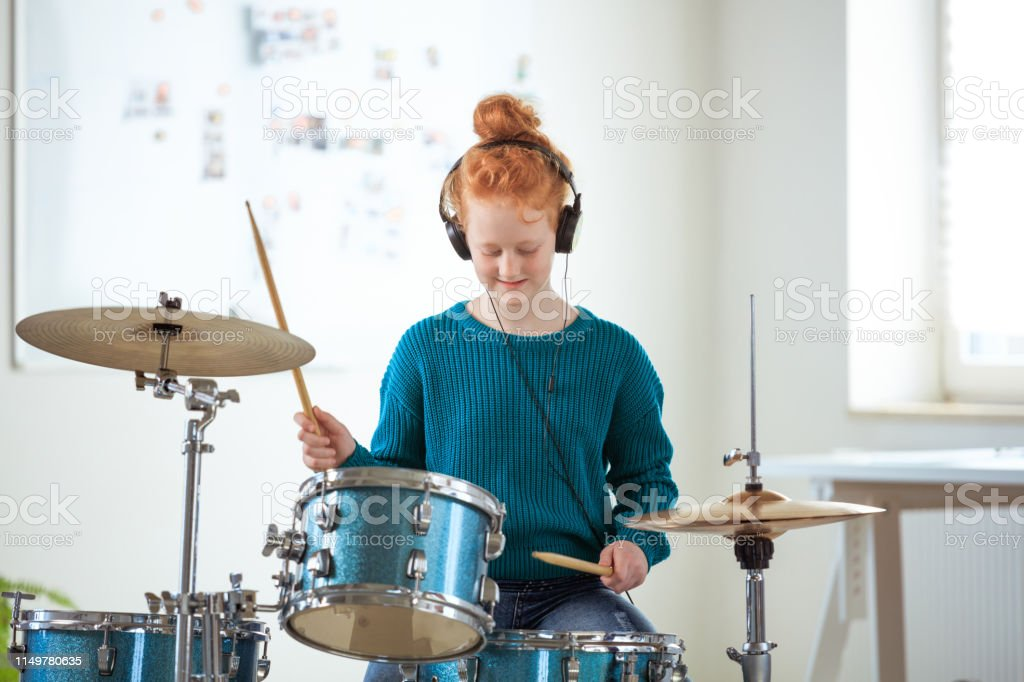 Confident drummer practicing while listening music Confident drummer listening music through headphones. Female student is practicing in training class. She is playing drums. 12-13 Years Stock Photo