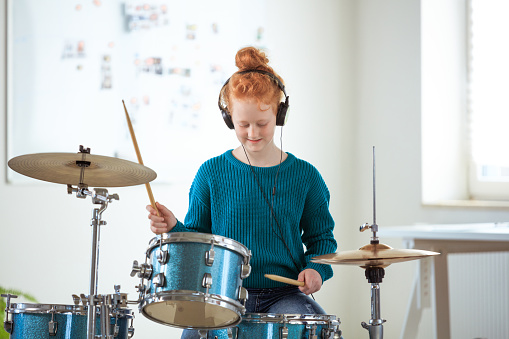Confident Drummer Practicing While Listening Music Stock Photo - Download Image Now