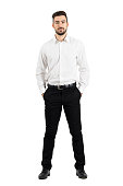 Confident elegant business man with hands in pockets looking at camera. Full body length portrait isolated over white studio background