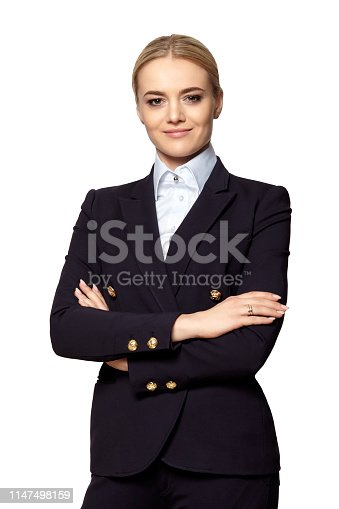 Studio portrait of young confident elegant businesswoman in a dark business suit stands with crossed hands.