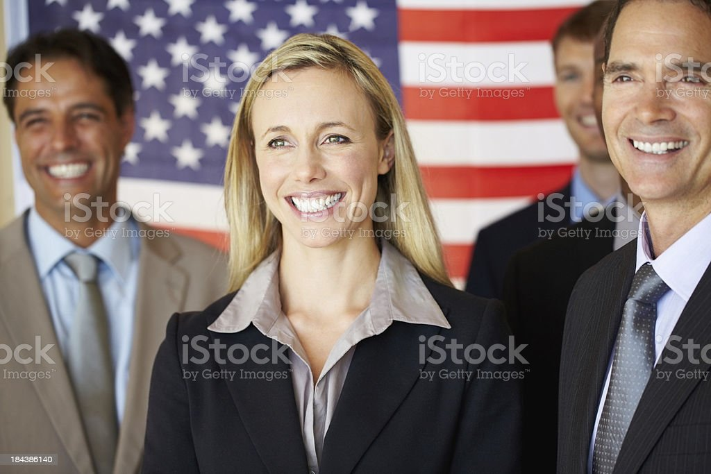 Confident executives smiling in front of flag stock photo