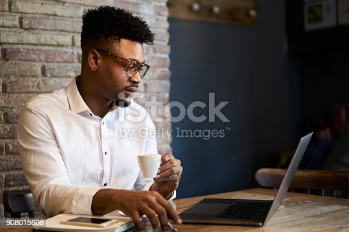 904263506 istock photo Confident experienced afro american administrative manager of restaurant checking financial documentation and weekly reports working with online database drinking coffee and using laptop computer 908015608
