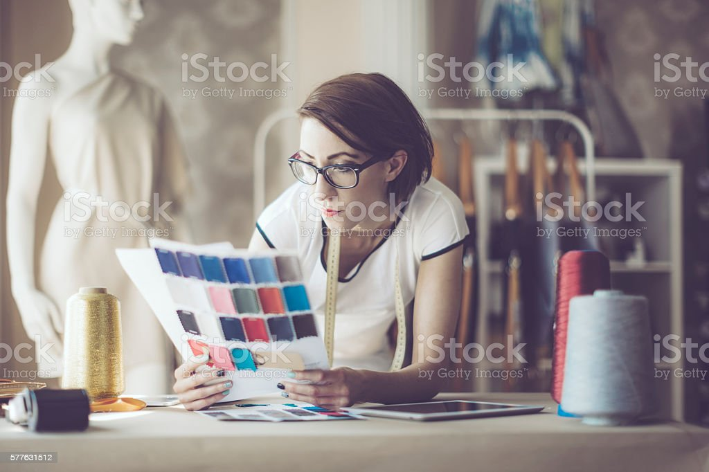 Confident fashion designer is working in her showroom. stock photo