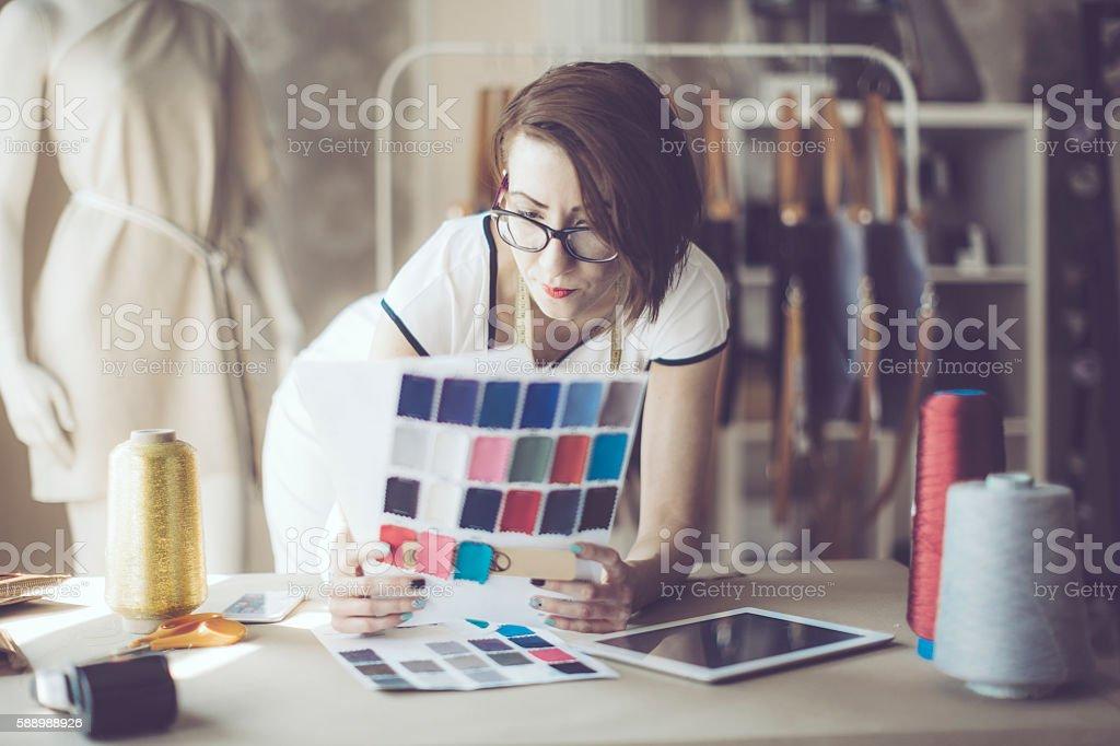 Confident fashion designer is working in her showroom. – Foto