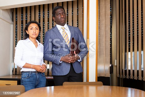 Portrait of successful confident female and male business partners of different nationalities standing in modern office