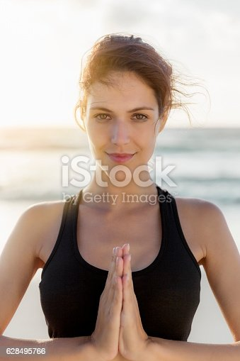 628497270 istock photo Confident female athlete doing yoga at beach 628495766
